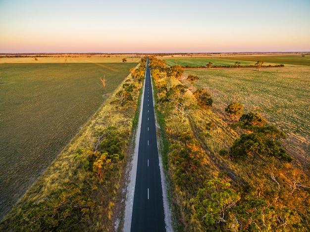 Estrada longa e reta na área rural entre campos verdes e pastagens ao pôr do sol
