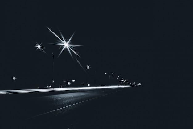 Estrada na cidade à noite com luzes de rua e longas faixas de luz de exposição do fundo dos carros