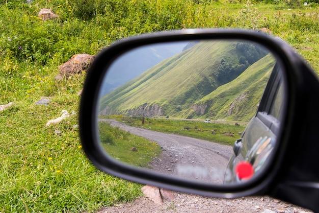 Estrada no espelho do carro, vista lateral