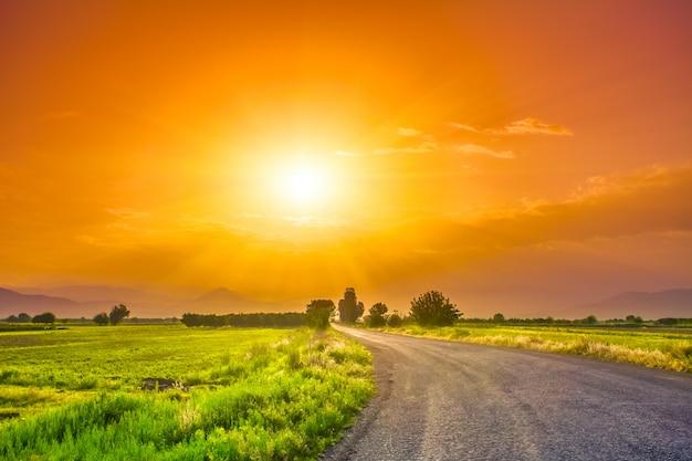 Estrada no prado com lindo céu pôr do sol