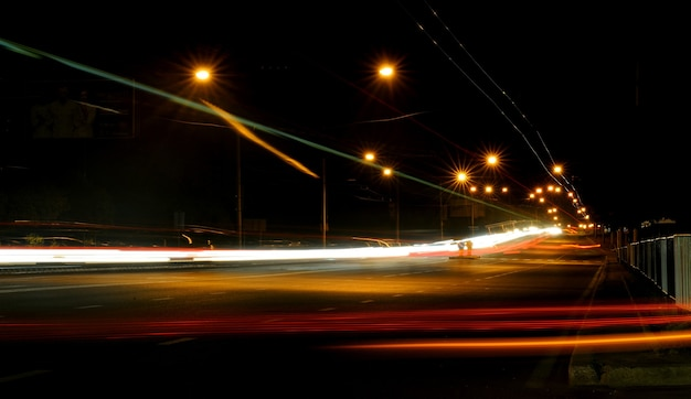 Estrada noturna na cidade com carro as trilhas leves