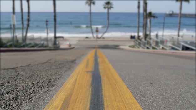 Estrada para a praia do oceano na califórnia, eua. palmeiras de verão. costa de verão perto de los angeles. ondas do mar.