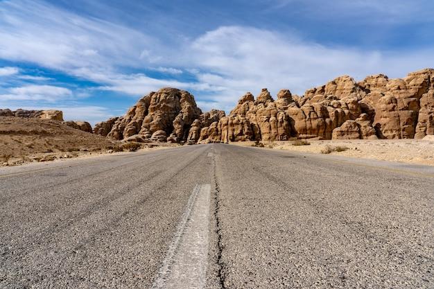 Estrada passando entre grandes penhascos sob um céu azul claro