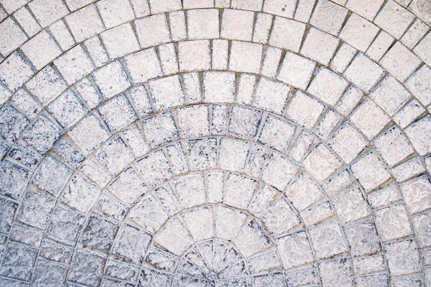 Estrada pavimentada com paralelepípedos arqueada com cursos de borda na textura da calçada