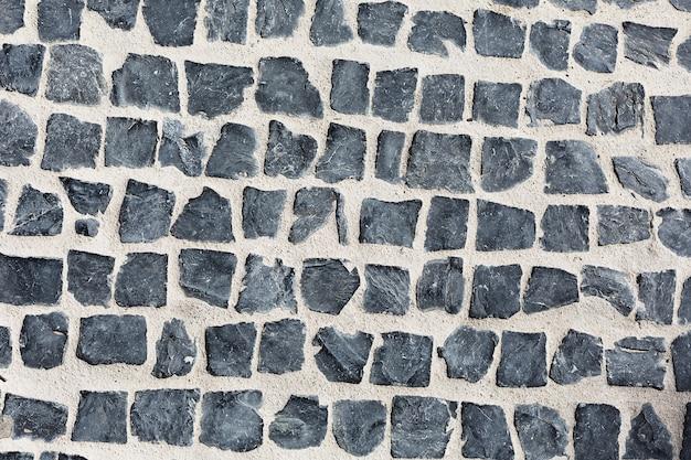 Estrada pavimentada de pedras quadradas cinza