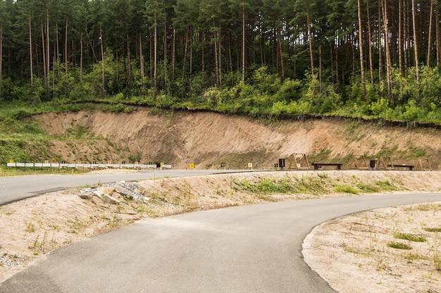 Estrada pavimentada para treinamento de verão de biatletas em campo de treinamento de tiro no meio da floresta, com alvos e alvos, a céu aberto, altai, belokurikha, base esportiva de biatlo.