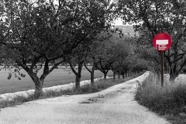 Estrada privada com placa de direção vertical proibida vermelha, foto em preto e branco