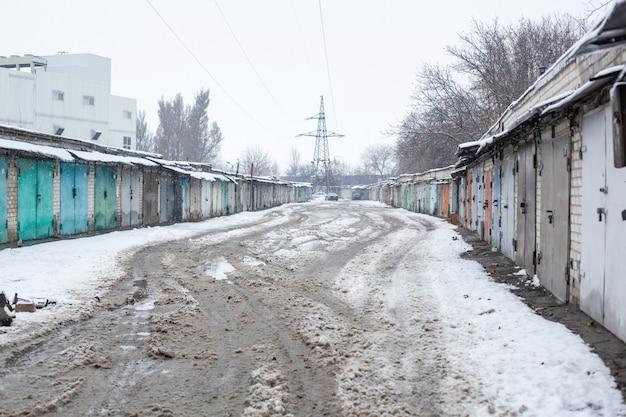 Estrada quebrada suja do inverno em uma garagem cooperativa. inverno deprimente temperamental cinzento