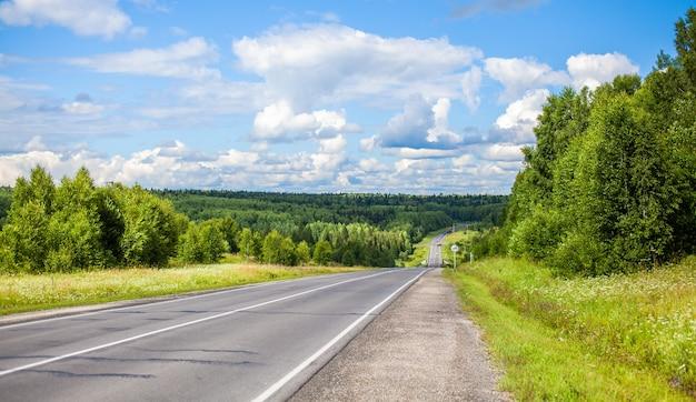 Estrada reta com uma marcação no fundo da natureza. estrada aberta no futuro, sem carros, auto na estrada de asfalto através de uma floresta verde, árvores. nuvens no céu azul no verão, sol, dia ensolarado. vista de baixo