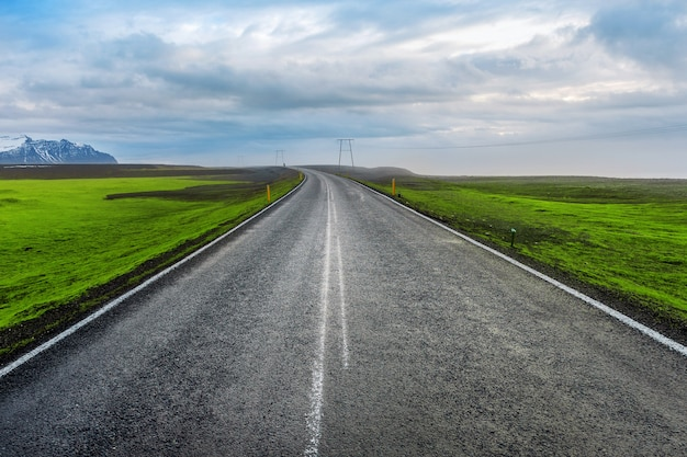 Estrada reta longa e céu azul.