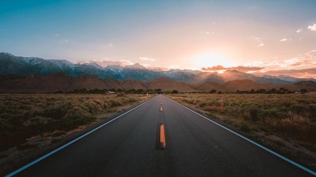 Estrada reta no meio do deserto com montanhas magníficas e o pôr do sol
