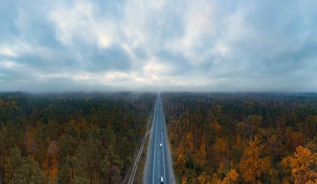 Estrada rodoviária com carros passando na floresta de outono, com céu escuro mal-humorado com nuvens de vista aérea.