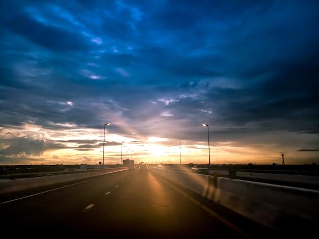 Estrada rodoviária, conceito de roadtrip de transporte. na via expressa de asfalto com o nascer do sol