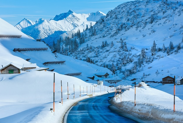 Estrada rural de montanha de inverno com declive nevado (áustria, tirol).