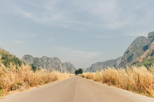 Estrada rural do sudeste asiático com paisagem de campo e montanhas