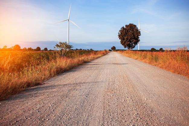 Estrada rural em um campo com turbinas eólicas.