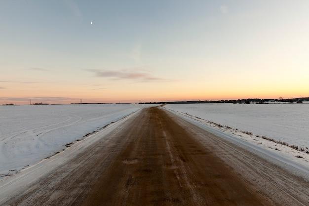 Estrada rural passando por campos agrícolas, substituída por neve branca após uma queda de neve, na estrada há muita sujeira e terra de neve derretida