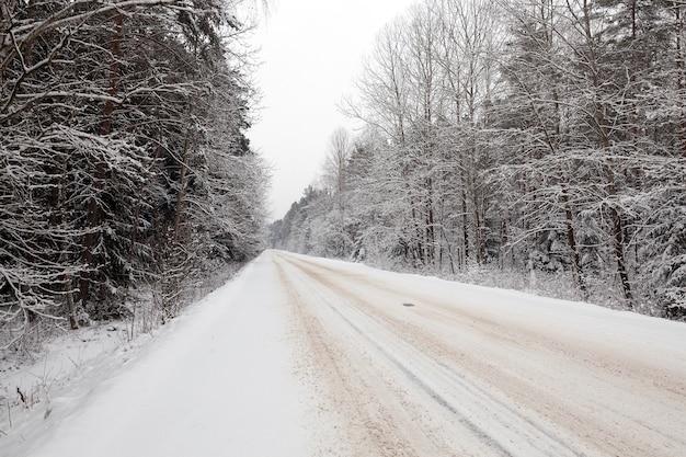 Estrada rural pela floresta no inverno. a foto foi tirada após uma nevasca. na superfície da pista dos carros