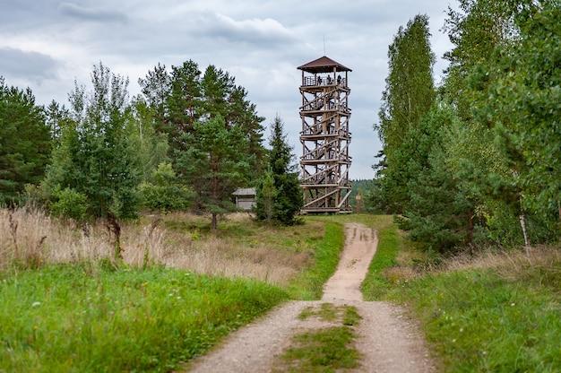 Estrada rural que leva à torre de observação de madeira na margem do rio daugava