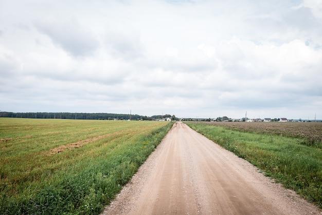 Estrada rural vazia cercada por campos de verão