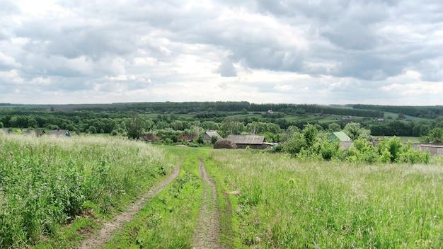 Estrada secundária através do campo verde na vila