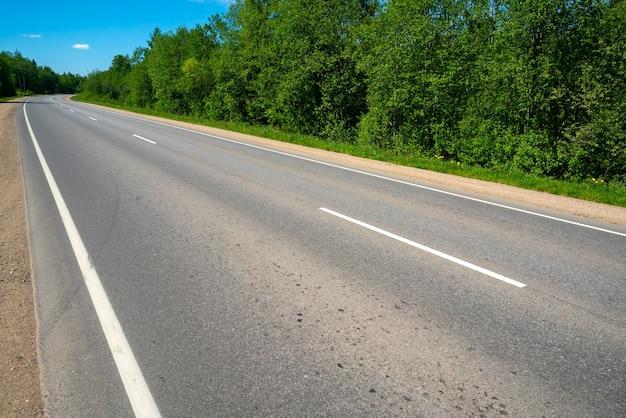 Estrada secundária de asfalto. marcações rodoviárias. dia ensolarado de verão.