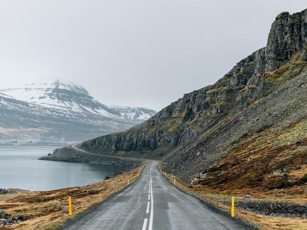 Estrada sinuosa cercada pelo mar e rochas cobertas por vegetação e neve sob um céu nublado