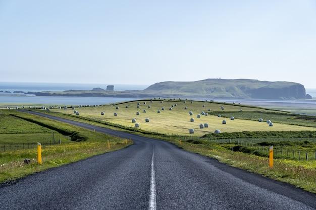 Estrada sinuosa cercada por colinas e mar sob a luz do sol na islândia