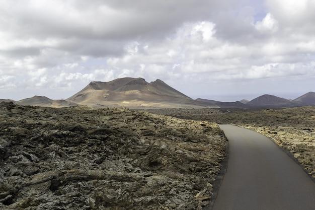 Estrada sinuosa cercada por colinas sob um céu nublado no parque nacional de timanfaya, na espanha