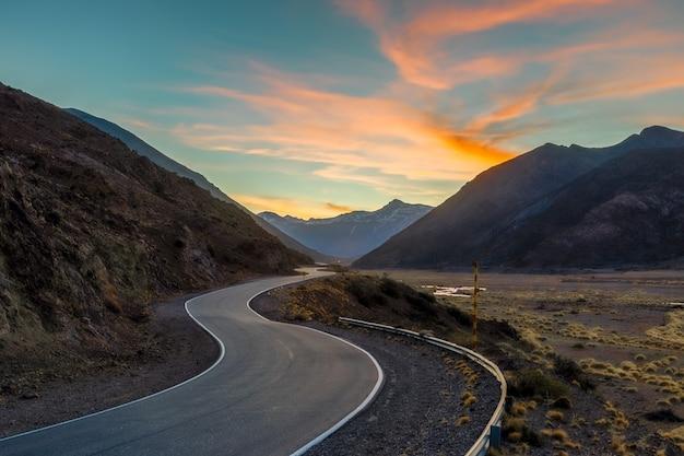 Estrada sinuosa, entre montanhas ao pôr do sol.