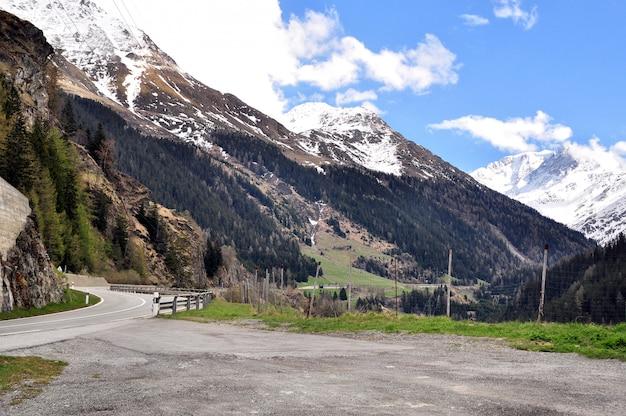 Estrada sinuosa entre picos de montanhas cobertas de neve
