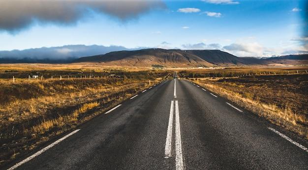 Estrada solitária islandesa em território selvagem sem ninguém à vista