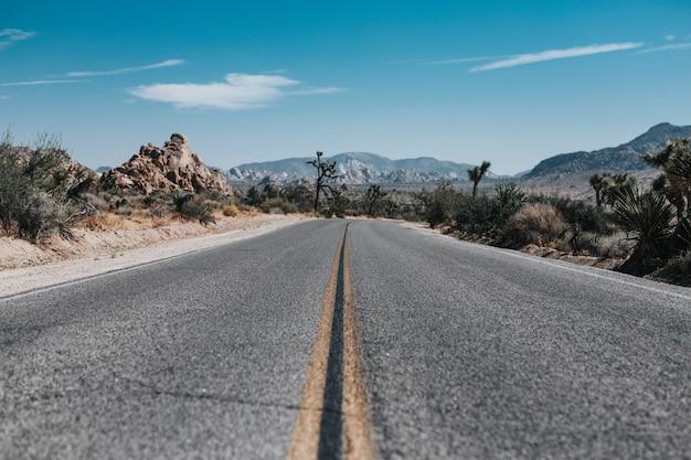 Estrada vazia com montanhas à distância sob um céu azul