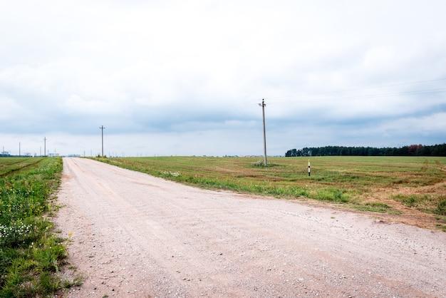 Estrada vazia, rodeada por um campo de verão.
