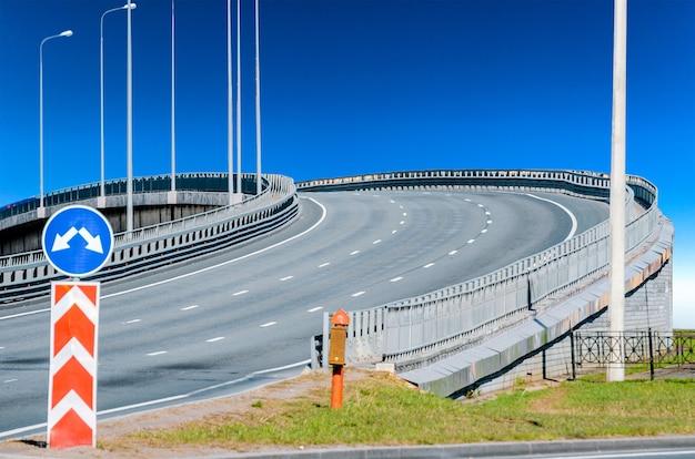 Estrada viaduto marcando asfalto e sinal de trânsito.