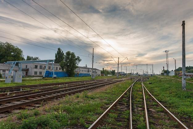 Estradas de ferro contra o céu bonito no por do sol. paisagem industrial com entroncamento ferroviário. industria pesada