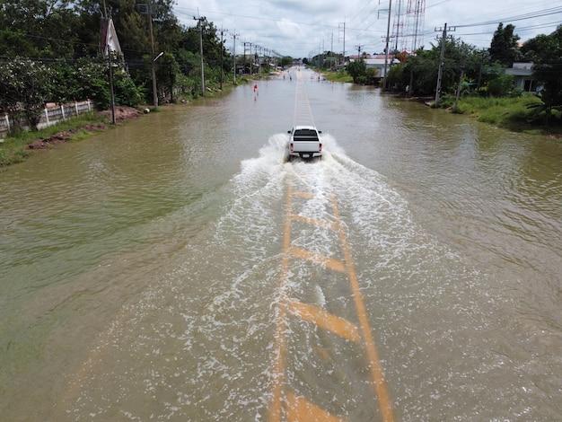 Estradas inundadas, pessoas com carros passando. fotografias aéreas de drones mostram ruas inundando e carros de pessoas passando, espirrando água.