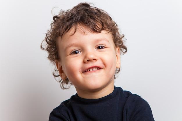 Estraga um garoto bonito e encaracolado, uma criança. sorriso engraçado