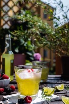 Estragão refrescante, amora e framboesa limonada com gelo na mesa rústica de madeira eu