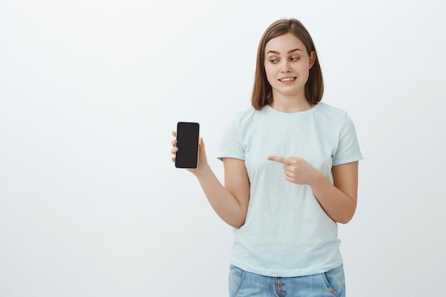 Estranha e fofa aluna em uma camiseta da moda e jeans segurando um smartphone apontando para a tela do telefone enquanto mostra uma foto estranha de um amigo em pé sobre uma parede cinza