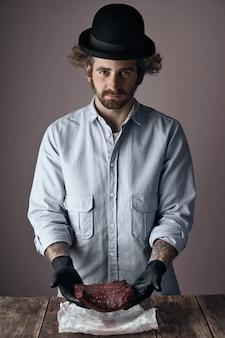 Estranho, jovem açougueiro judeu com cabelo encaracolado e barba, usando um chapéu-coco muito pequeno e camisa jeans desbotada, oferece um bife cru kosher nas mãos sobre uma mesa de madeira.