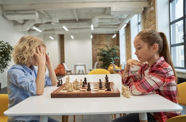 Estratégia concentrada menino e menina desenvolvendo estratégia de xadrez jogando jogo de tabuleiro sentados juntos em
