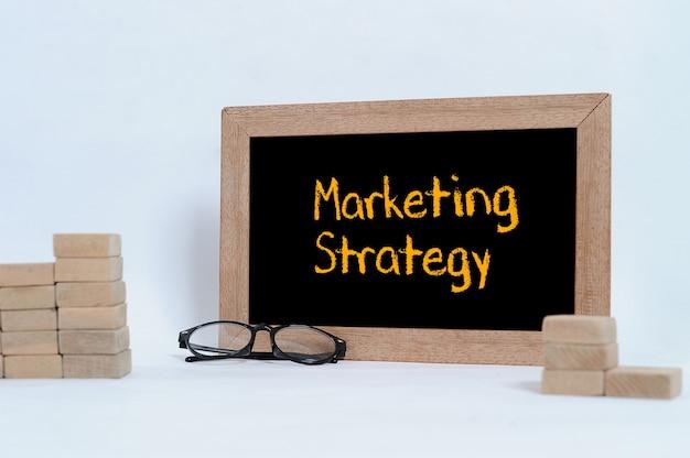 Estratégia de marketing inscrição no quadro-negro óculos e bloco de madeira empilhamento como degrau