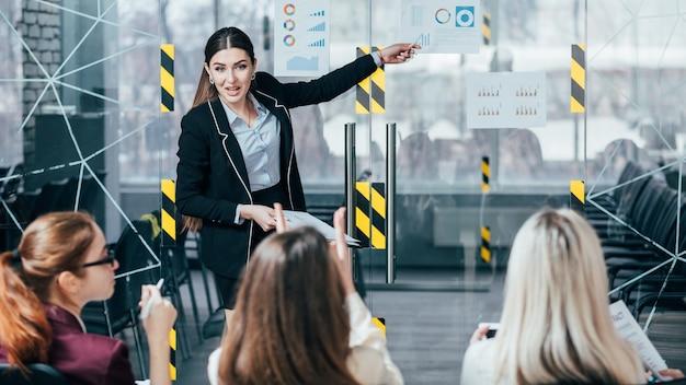 Estratégia de negócios bem-sucedida. apresentação do palestrante. líder da equipe apontando para documentos com diagramas de receita.