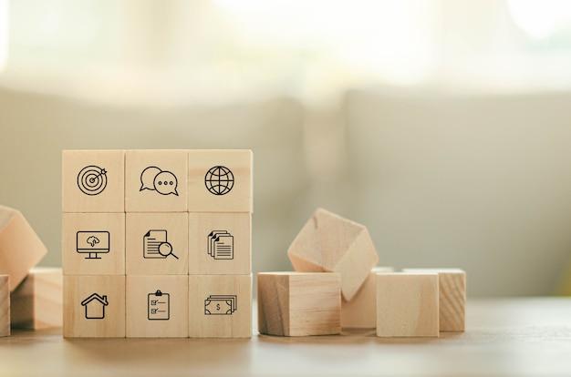 Estratégia de negócios com blocos de madeira e objetivos e metas do plano de ação de vikon de finanças de negócios pilha em cima da mesa sobre estratégias de negócios e planos de ação.