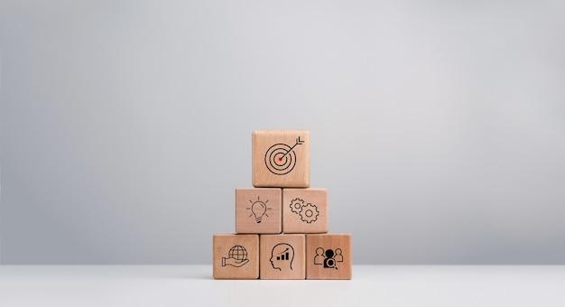 Estratégia de negócios com processo de sucesso de crescimento para o conceito de liderança e trabalho em equipe. o plano de ação, ícone de alvo de negócios em blocos de cubo de madeira empilham a forma de pirâmide em fundo branco.