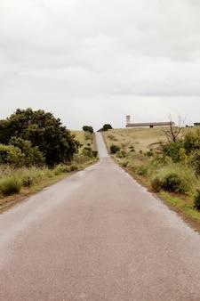Estreita estrada pavimentada no campo com um céu clody