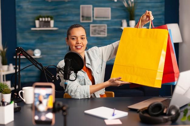 Estrela da mídia social fazendo giweaway de presentes para assinantes leais. criador de conteúdo criativo fazendo conceito de blog de vídeo falando e olhando para uma câmera profissional em podcast de estúdio doméstico