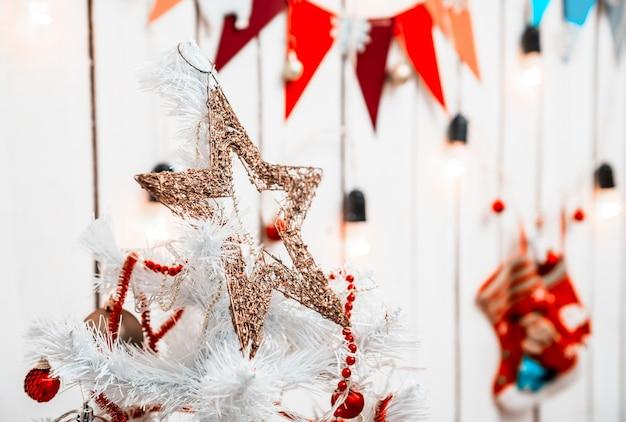 Estrela de brinquedo dourada no topo da árvore de natal branca em um quarto decorado