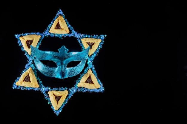 Estrela de david com máscara e biscoitos. símbolo judeu em fundo preto.